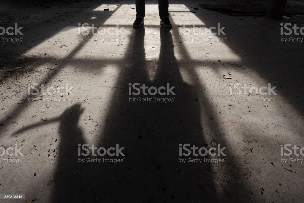 Sombra de um homem com grande faca na mão, dentro de alguns buiding escuro, assustador - foto de acervo