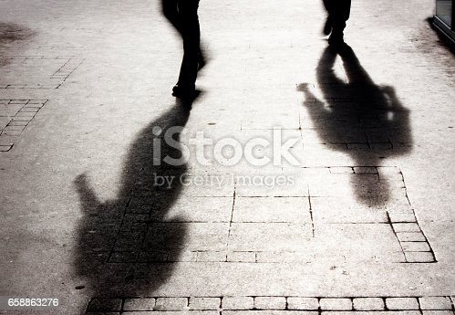 istock Shadow of a man on patterened sidewalk 658863276