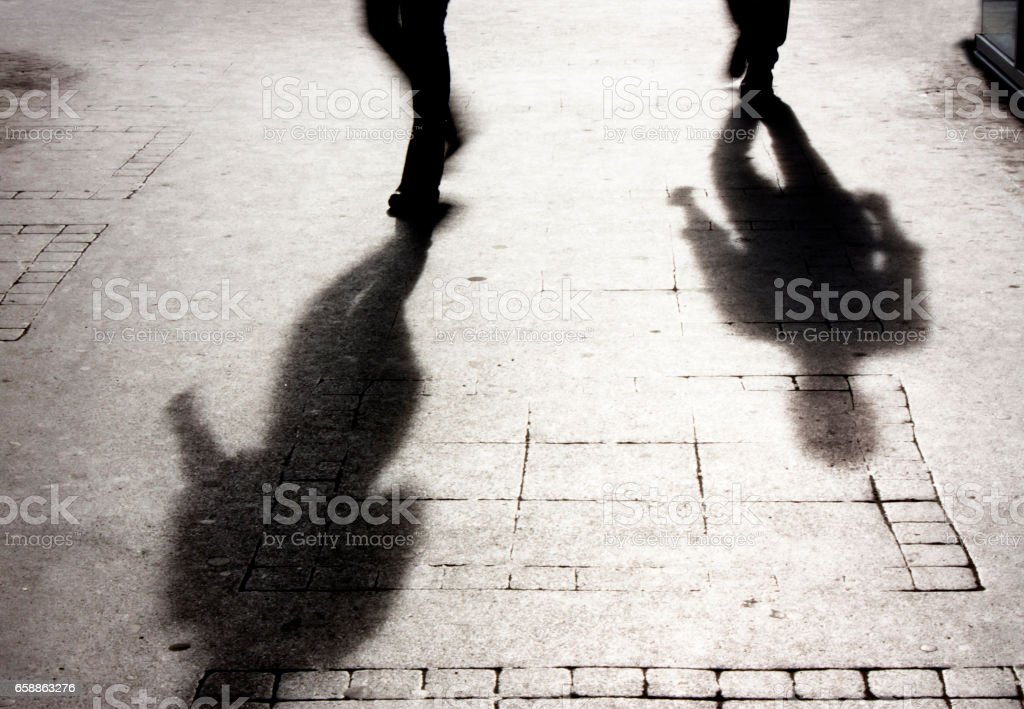 Shadow of a man on patterened sidewalk stock photo
