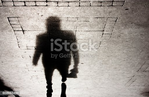 Upside down shadow of a man approaching on pattered sidewalk, in black and white