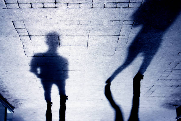 Shadow of a man on patterened sidewalk