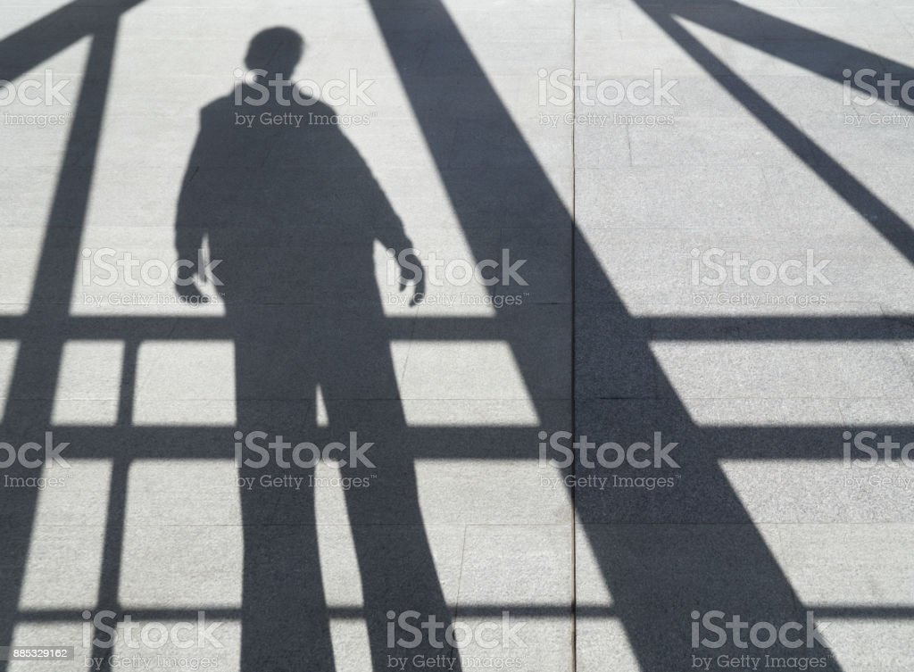 shadow of a man on the sidewalk among the beams royalty-free stock photo