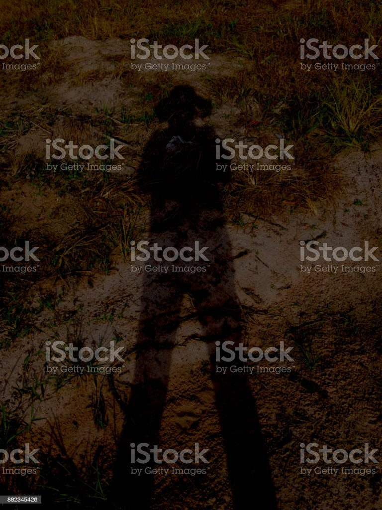 Shadow of a man standing and wearing a hat looked like a ghost, which looked horrible. stock photo