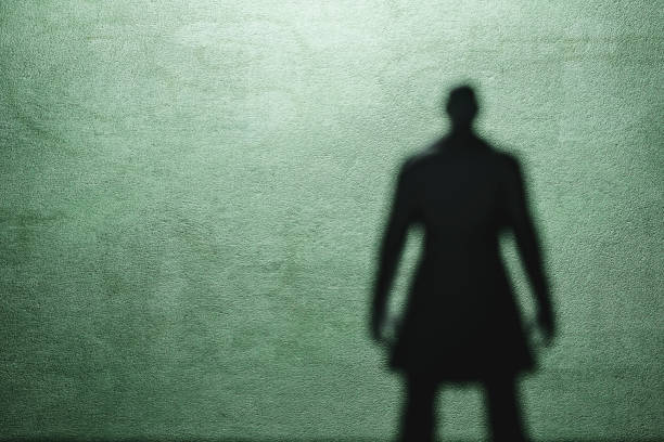 Shadow of a spooky man in trench coat Shadow of a spooky man in trench coat. creepy stalker stock pictures, royalty-free photos & images