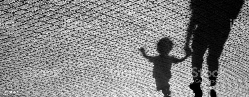 Shadow of a toddler and a man stock photo