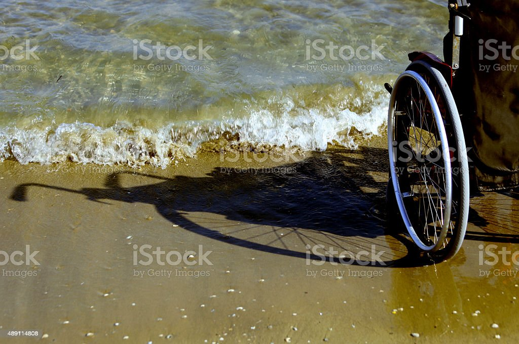 shadow of a wheelchair in the sand on the seashore stock photo