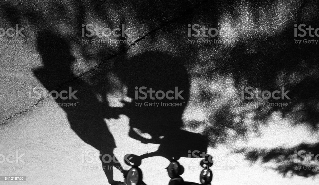 Shadow of a woman pushing a baby trolley stock photo