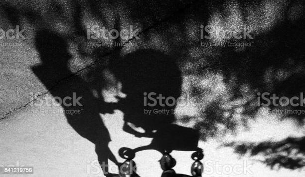 Photo of Shadow of a woman pushing a baby trolley