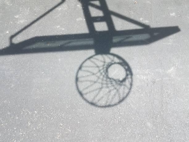 shadow of basketball hoop with net on asphalt stock photo
