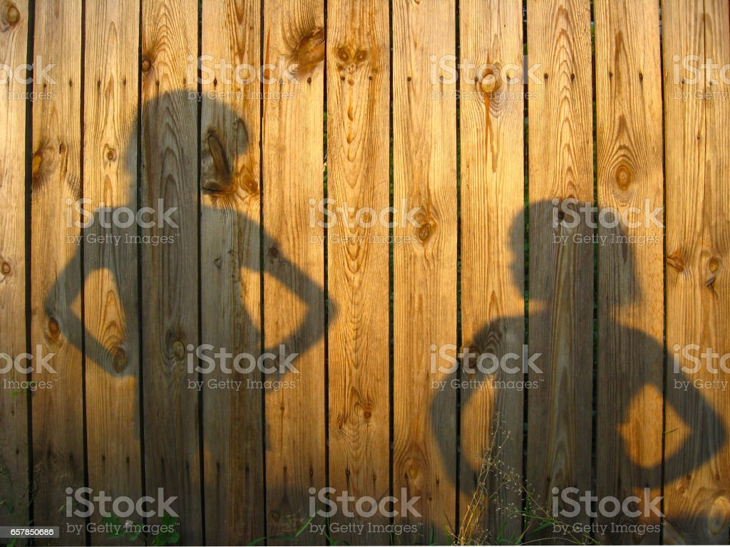 Shadow of boy and girl staring each other on wooden surface stock photo