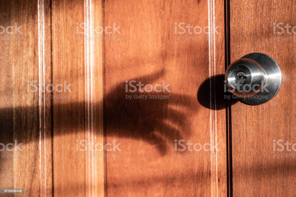 Shadow of burglar's hand trying to open the door stock photo