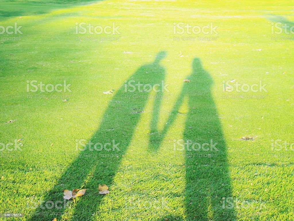 shadow of couple holding hands stock photo