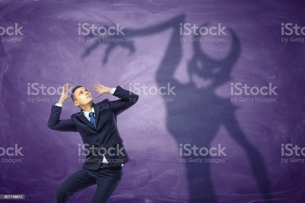 Shadow of devil trying to catch the frightened businessman stock photo