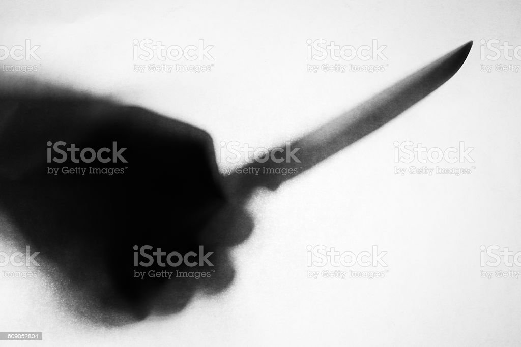 shadow of hand holding knife stabbing someone stock photo
