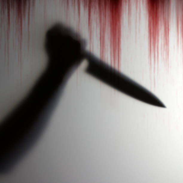 Shadow of hand holding knife to pierce the victim behind a transparent object with bloody background scary stock photo