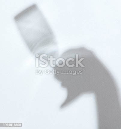 Shadow of hand with wine glass on white wall background