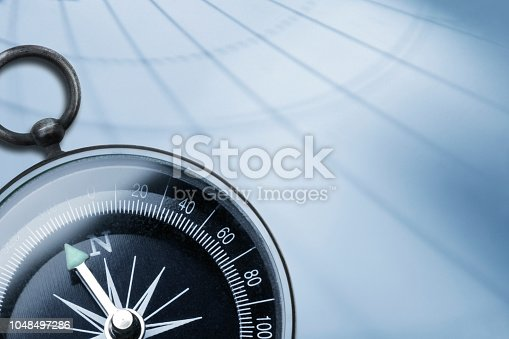 A compass rests on a light blue background as the lines of latitude and longitude are cast across it.