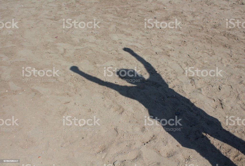 Shadow of man doing socialism sign on sand background. Raised fist is a symbol of solidarity and support. It is also used as a salute to express unity, strength, defiance, or resistance. stock photo