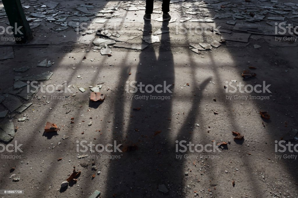 Shadow of maniac killer holding knife in dark, spooky, messy, abandoned building stock photo