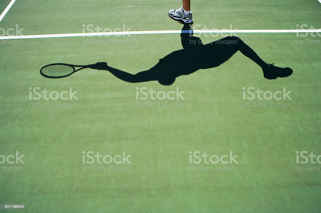 Shadow of person playing tennis stock photo