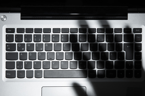 Shadow Of Persons Hand Falling On Laptop Keypad Stock Photo - Download Image Now