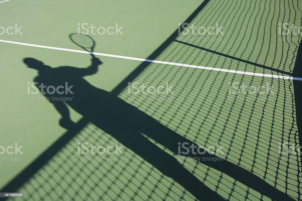 Shadow of senior man playing tennis on court stock photo