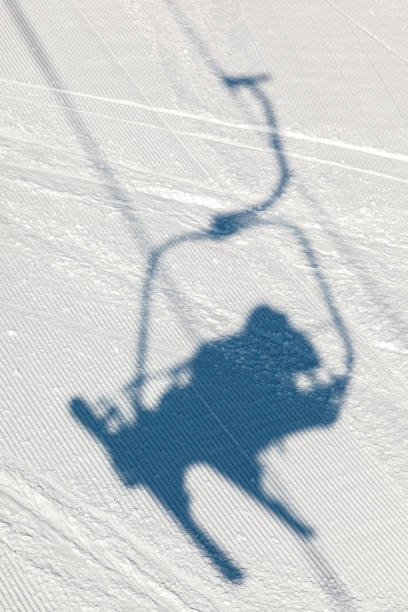 Shadow of skier on a chairlift stock photo