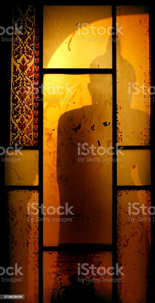 Shadow of the Buddha in the window stock photo