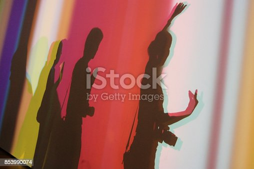 istock shadow of three happy people make Buddhist hand sign posting on white wall with colorful light spots 853990074