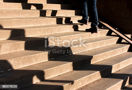 812812808istockphoto Shadow of three people on city stairs 862076220