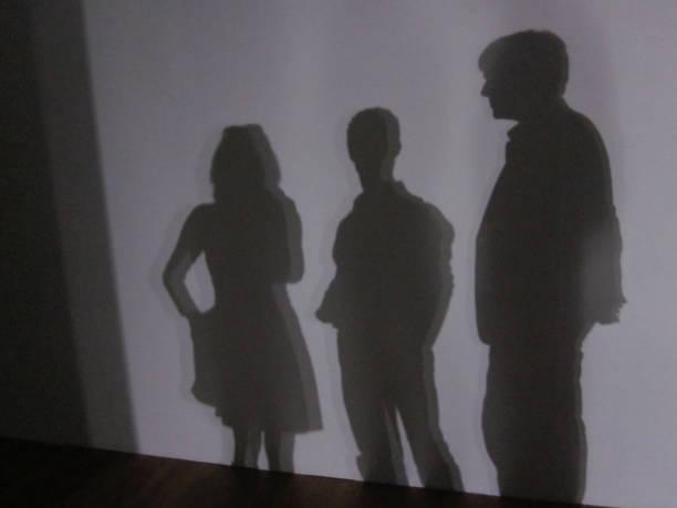 schaduw van drie mensen die staan voor een witte muur foto