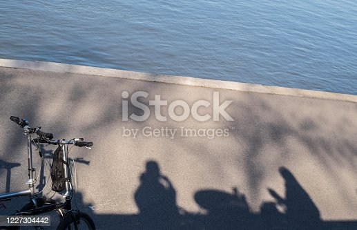 667005568 istock photo Shadow of unrecognizable cyclist, on the shore in a restaurant 1227304442