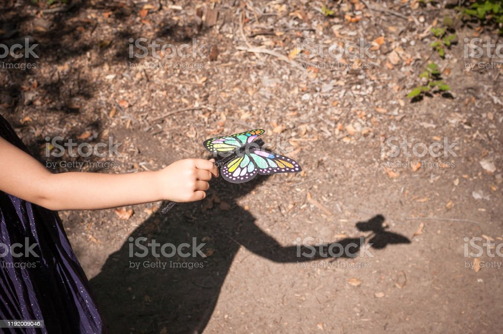Shadow of young girl playing with her toy butterfly outdoors - Royalty-free 6-7 Years Stock Photo