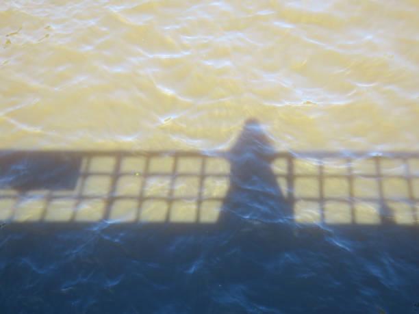 schaduw op het water, portret dat van een brug wordt genomen foto