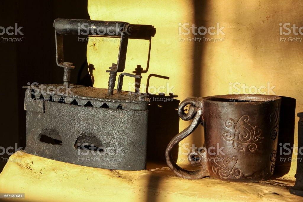 Shadow play with an old flat iron and vintage iron cup stock photo
