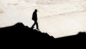 istock Shadow silhouette of a man walking alone down city stairs 1215138372