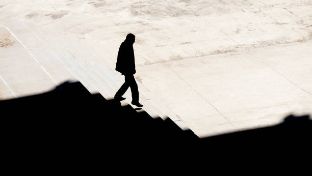 Shadow silhouette of a man walking alone down city stairs