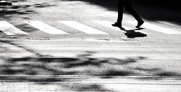 silhouette d'ombre d'une personne traversant la rue - motion blurred pedestrians crossing sunlit street photos et images de collection
