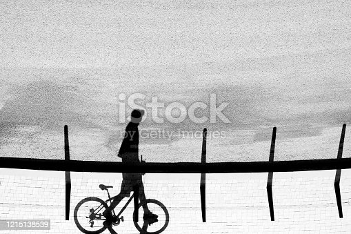 812812808 istock photo Shadow silhouette of a young man walking and pushing his bicycle, in black and white 1215138539