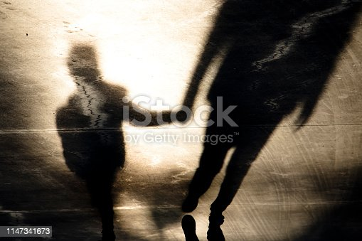 istock Shadow silhouettes of father and son walking hand in hand 1147341673
