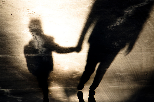 Shadow silhouettes of father and son walking hand in hand