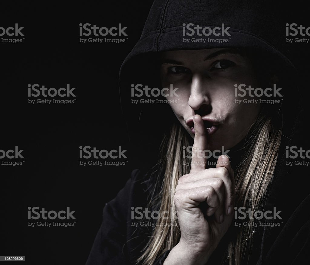 Shadowed woman asking for silence royalty-free stock photo