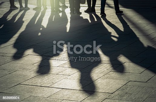 istock Shadows and silhouettes of people at a city during sunset 853989924
