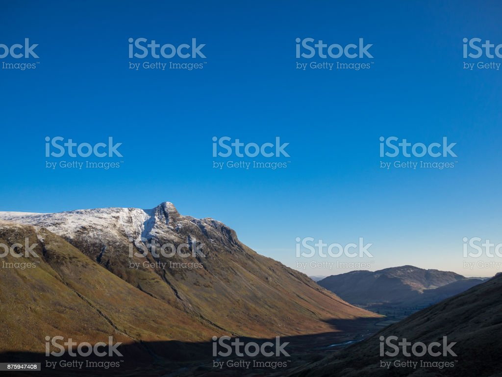Shadows and Snow covered peaks in Langdale Valley Lake District stock photo