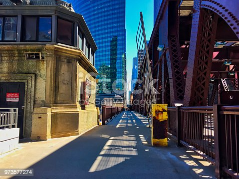 Shadows from el tracks splay across Lake Street drawbridge in Chicago Loop. Chicago Bridgehouse on left guards the Chicago River, and elevated track for the 'el train runs above the street on the right.