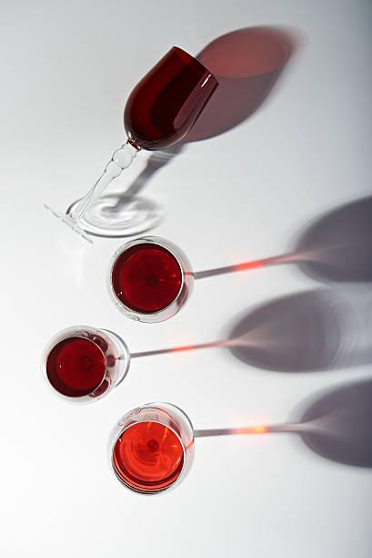 shadows from wine glasses - rotes oberteil stock-fotos und bilder