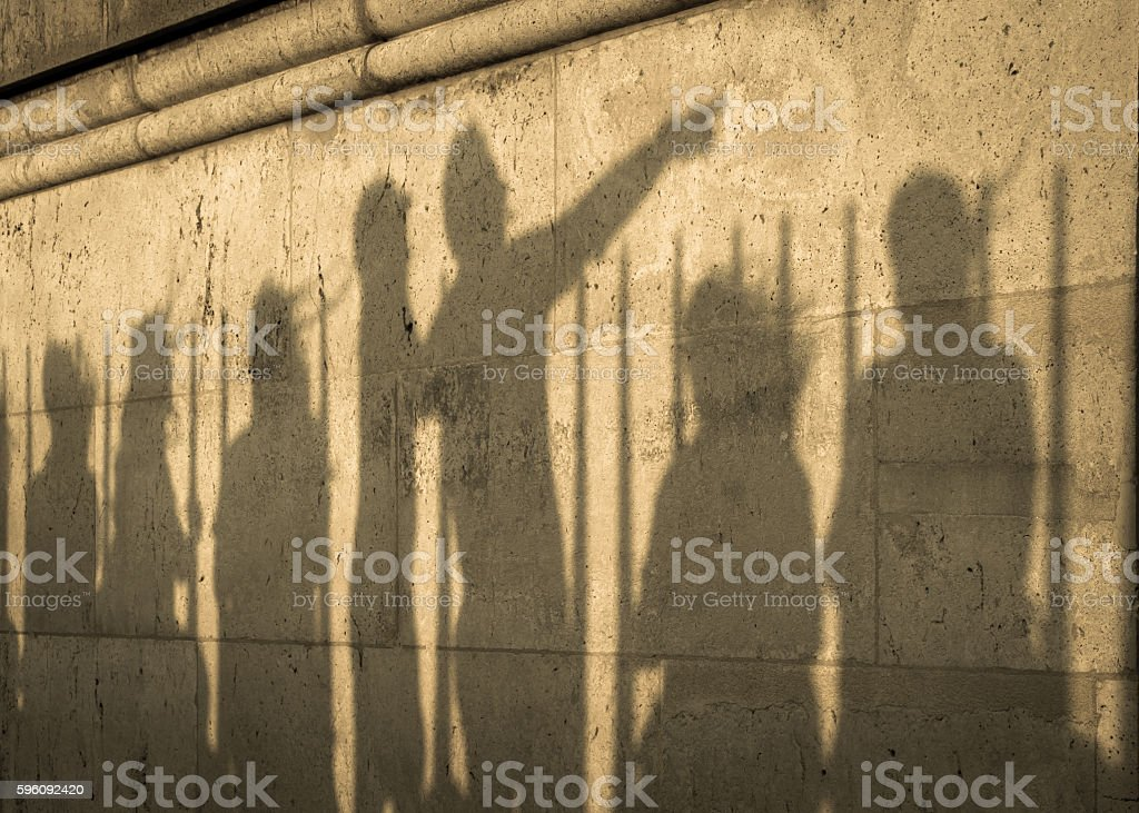 Shadows of 7 people (one of whom is pointing) royalty-free stock photo