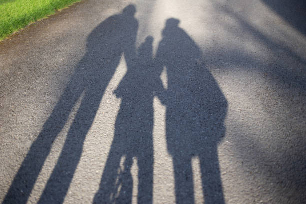 shadows of a family on a walk in the park stock photo