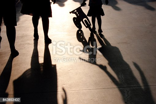812812808 istock photo Shadows of a family with little girl pushing a bike 842853402
