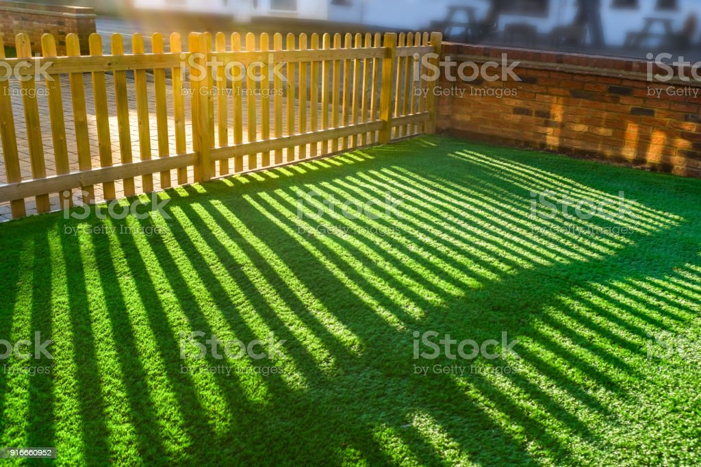 shadows of a wooden picket fence on an artifical grass lawn stock photo